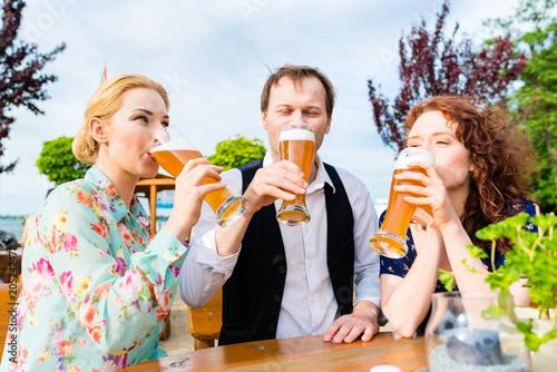 Poster Happy friends toasting with beer in garden restaurant