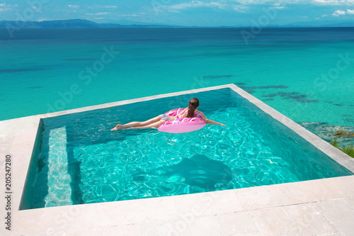 Sexy girl relaxing on inflatable pink donut in the infinity swimming pool at luxurious villa resort. Summer holiday idyllic top view. Beautiful destination. Travel concept.