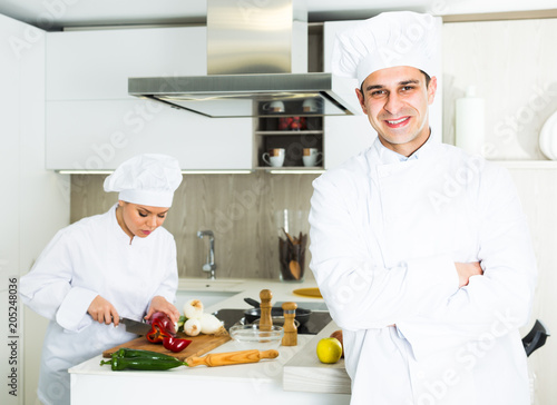 Male chef in white uniform standing near workplace on kitchen