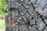 Foreground of old iron door with iron handle. Old rusty gate handle on wooden door. - 205248246