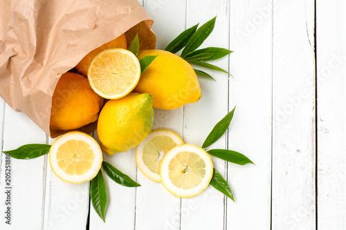 Lemons in a paper bag on a light background.