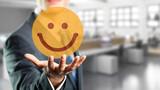 Geschäftsmann präsentiert lächelnden Smiley vor Bürohintergrund