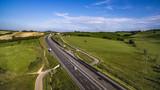 Italia, Maggio 2018 - Vista aerea dell'autostrada con automobili e camion che attraversa le colline con i campi di grano non ancora maturo