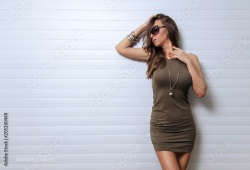 Elegant young adult woman in summer dress and sunglasses posing at sunset