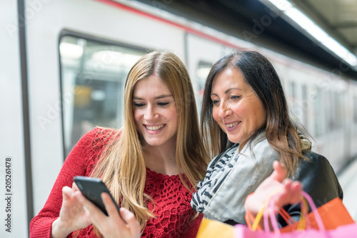 Happy beautiful blonde girl showing pictures to her mother inside subway station. Tourism and holiday concept
