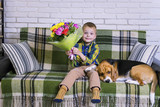 funny boy with a bouquet of flowers and a dog Beagle on the sofa