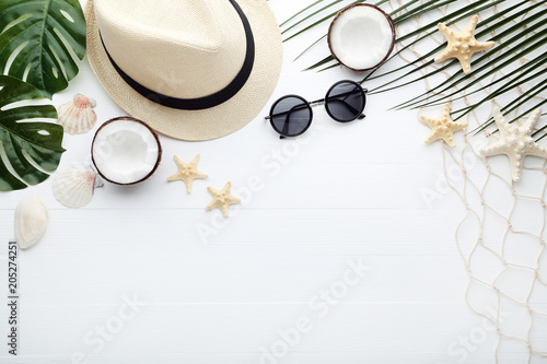 Summer accessories with coconuts and green leafs on wooden table