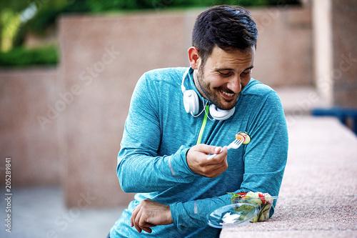 Fototapeta Man is eating vegetable salad