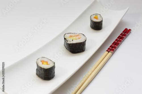 Plexiglas Sushi bar Tres piezas de sushi con palillos