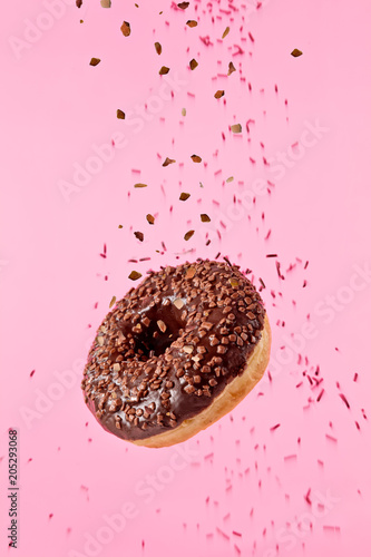 Flying sweet donut isolated on pink background.
