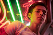 Young man, lit by neon light at night.