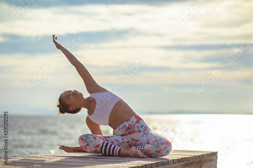 Fotobehang School de yoga younger woman playing yoga pose on sea pier