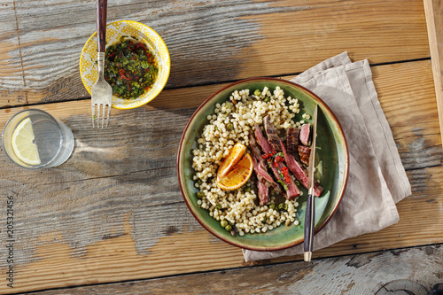 Plexiglas Steakhouse Healthy dinner table concept Beef steak grilled pearl barley couscous wooden table sauce water with lemon top view