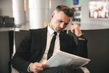 Pensive businessman reading newspaper