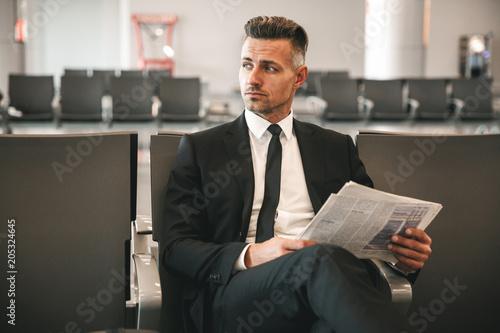 Serious businessman reading newspaper