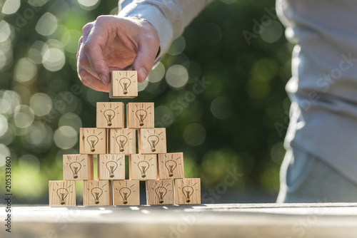 Foto Murales Vision and ideas concept of a man building a pyramid of wooden blocks with light bulb icons