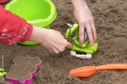 Children's sandbox, kids play sand building locks close-up