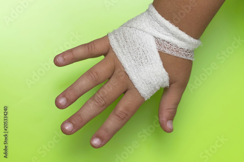 Children's arm bandaged with a white bandage on a green backgrou