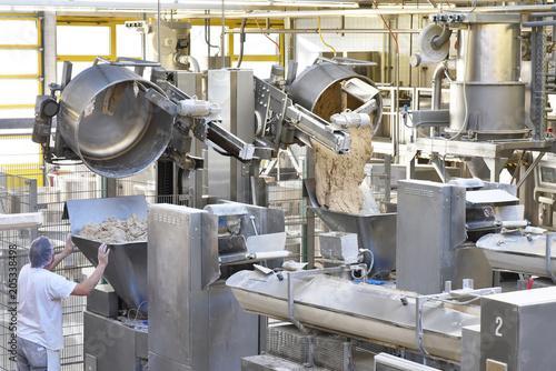 Fototapeta Arbeiter bedient Knetmaschinen in einer Großbäckerei - industrielle Herstellung am Fliessband von Brot in der Lebensmittelindustrie // kneading machines in a large bakery - food industry
