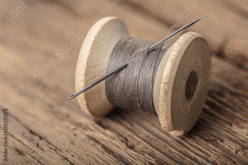 spool of thread with a needle - 205339272