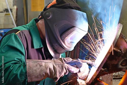 Schweißer am Arbeitsplatz in einer Werkstatt schweißt Metall // Welder at the workplace in a workshop welds metal