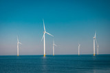 Offshore and Onshore Windmill farm in the ocean ,windmills isolated at sea on a beautiful bright day Netherlands Flevoland Noordoostpolder  - 205346815