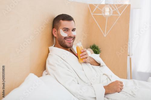 Czas rekreacyjny. Pozytywny szczęśliwy mężczyzna pije sok pomarańczowego podczas gdy relaksujący w domu