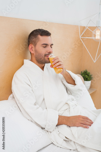 Healthy drink. Nice peaceful man drinking juice while resting at home