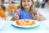 Young girl eat pizza outdoors