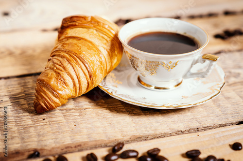 Plexiglas Koffiebonen cup of delicious and fragrant coffee with a tasty croissant on a wooden table