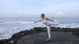 Wide shot of mature woman in white doing dancers yoga pose on coastline in morning - 205386040