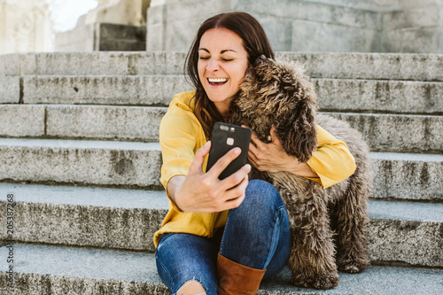 Young beautiful woman taking photograph of her sweet dog playfuly in a lovely park of the center of Madrid. Seated in stone stairs. Lifestyle © lubero