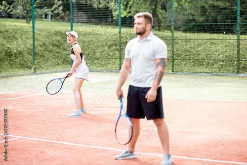 Fotobehang Tennis Young couple in white sports wear playing tennis on the tennis court outdoors
