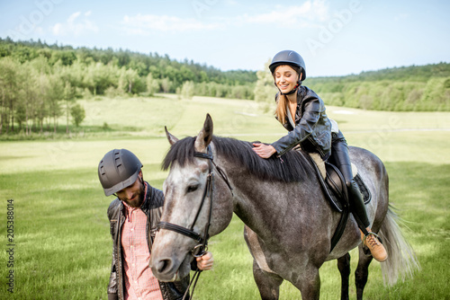 Man leading a horse with woman rider on the beautiful green meadow during the sunny weather