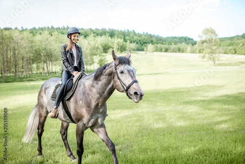 Woman in leather jacket with protective helmet riding a horse on the green meadow