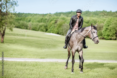 Fototapeta Handsome man in leather jacket with protective helmet riding a horse on the green meadow