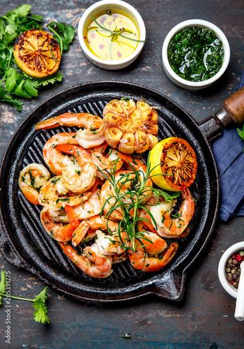 Fototapeta Grilled shrimps prawns on vintage grill pan, top view. Dark background