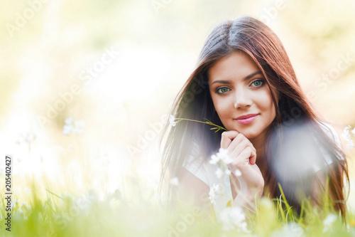 Ładna brunetki dziewczyna kłaść na trawie