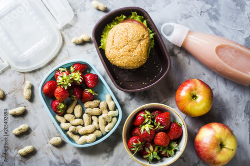 Cooking lunch for the child to school. On the gray kitchen table. Sandwich, strawberries and peanuts in lunchboxes. Top view. - 205402694