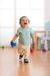 Leinwanddruck Bild - Cheerful baby toddler running in children room