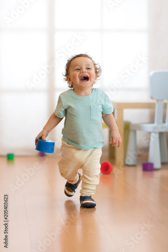 Leinwanddruck Bild Cheerful baby toddler running in children room