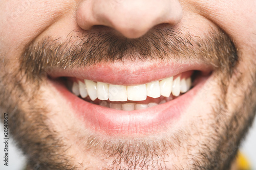 Detailed image of young man smiling with perfect white teeth. Healthy concept. Close-up.