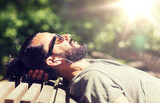 people, music, technology, leisure and lifestyle - hipster man with earphones listening to music on city street bench - 205412222