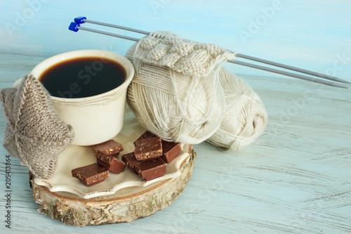 Przędza i druty na jasnoniebieskim tle. Czarna kawa i czekolada.
