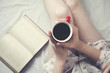 woman hand  cup of coffee and book