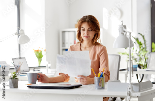 Poster business and people concept - businesswoman with papers at working office and drinking coffee