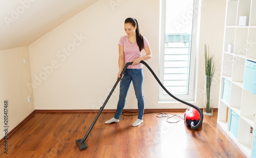 Foto Murales household, housework and cleaning concept - happy woman or housewife with vacuum cleaner at home