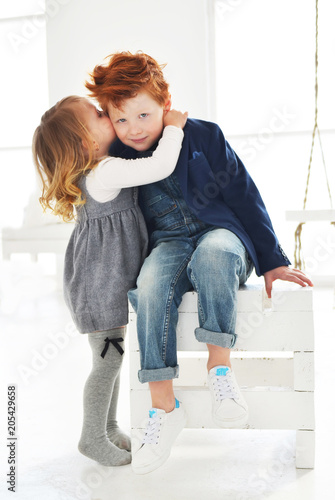Sister kissing her brother in the cheek. Cute blond baby girl and red boy brother in the white studio. Love in the family