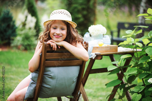 Poster happy child girl in hat enjoying warm summer day in the blooming garden, blooming hydrangea flowers on background