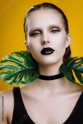 fashion photo girl with wet hair in swimsuit with black lips posing in studio on yellow background with a palm tree in her hands
